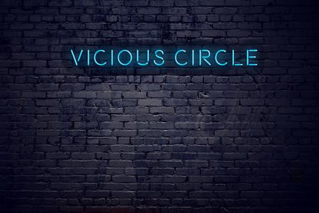 Brick wall and neon sign with text vicious circle.