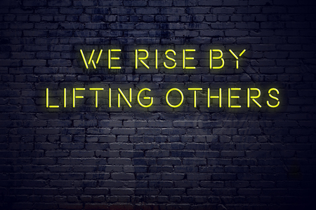 Positives inspirierendes Zitat auf Leuchtreklame gegen Backsteinmauer Wir erheben uns, indem wir andere anheben. Standard-Bild
