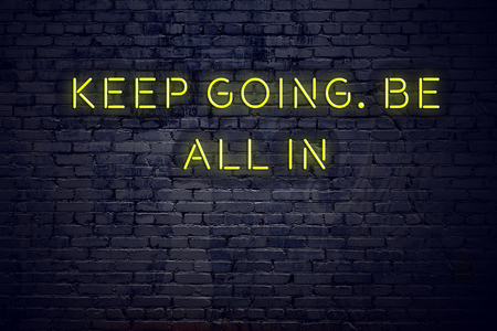 Positive inspiring quote on neon sign against brick wall keep going be all in. 免版税图像