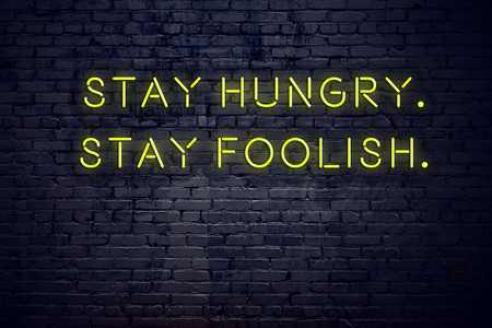 Positive inspiring quote on neon sign against brick wall stay hungry stay foolish. Banco de Imagens