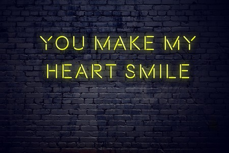 Positive inspiring quote on neon sign against brick wall you make my heart smile. Zdjęcie Seryjne