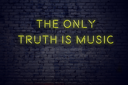 Positive inspiring quote on neon sign against brick wall the only truth is music.