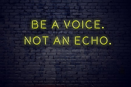 Positive inspiring quote on neon sign against brick wall be a voice not an echo.