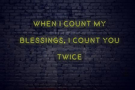 Pozytywny inspirujący cytat na neonowym znaku na ceglanej ścianie, kiedy liczę moje błogosławieństwa, liczę cię dwa razy.
