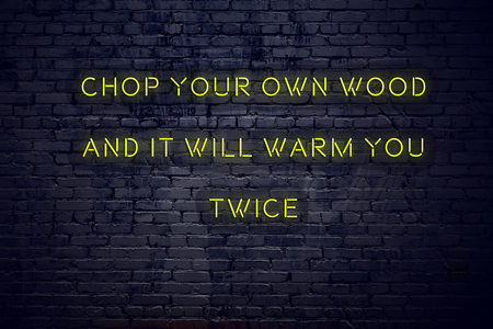 Positive inspiring quote on neon sign against brick wall chop your own wood and it will warm you twice.