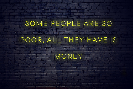 Positive inspiring quote on neon sign against brick wall some people are so poor all they have is money.