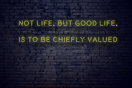 Positive inspiring quote on neon sign against brick wall not life but good life is to be chiefly valued.