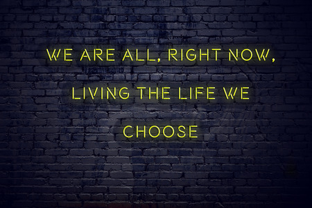Positive inspiring quote on neon sign against brick wall we are all right now living the life we choose.