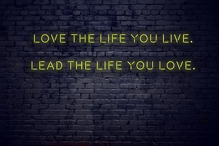 Pozytywny inspirujący cytat na neonowym znaku na ścianie z cegły kochaj życie, w którym żyjesz, prowadź życie, które kochasz.
