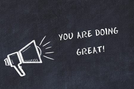 Chalk board sketch with loudspeaker and motivational phrase you are doing great. 免版税图像