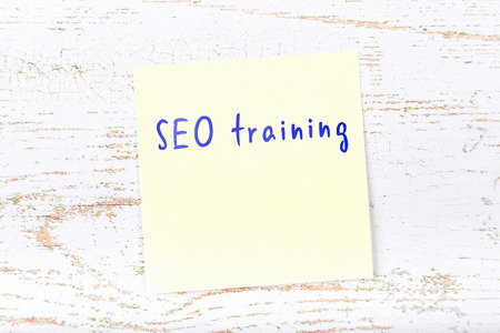 Yellow sticky note with handwritten text seo training. Imagens