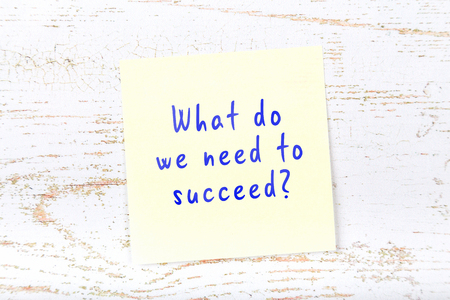 Yellow sticky note with handwritten text what do we need to succeed.