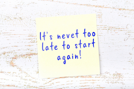 Yellow sticky note with handwritten text its nevet too late to start again. Stockfoto
