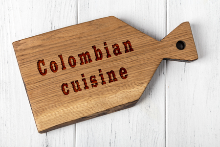 Wooden cutting board with inscription. Concept of colombian cuisine.