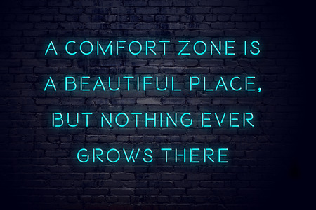 Night view of neon sign with motivational inscription about comfort zone.