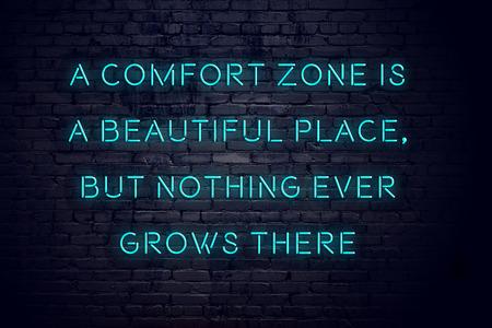 Vista nocturna del letrero de neón con inscripción motivacional sobre zona de confort.