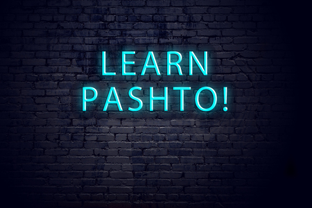 Brick wall and neon sign with inscription. Concept of learning pashto.