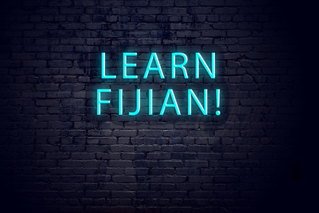 Brick wall and neon sign with inscription. Concept of learning fijian.