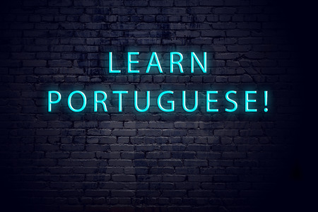 Brick wall and neon sign with inscription. Concept of learning portuguese.