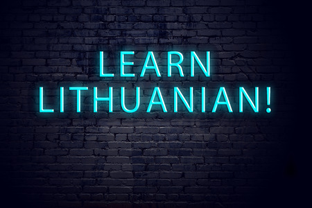Brick wall and neon sign with inscription. Concept of learning lithuanian.