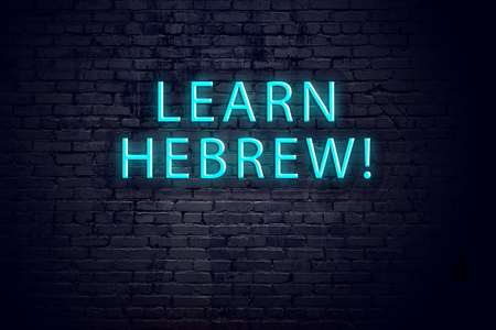 Brick wall and neon sign with inscription. Concept of learning hebrew.