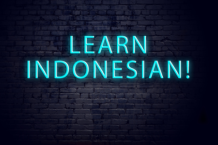 Brick wall and neon sign with inscription. Concept of learning indonesian.