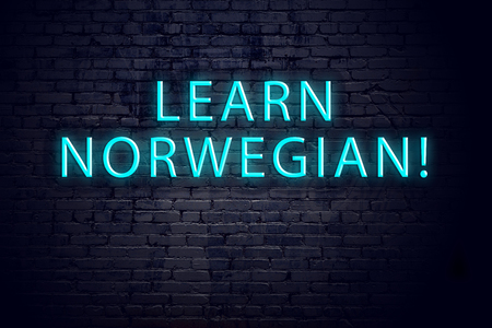 Brick wall and neon sign with inscription. Concept of learning norwegian.