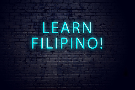 Brick wall and neon sign with inscription. Concept of learning filipino.