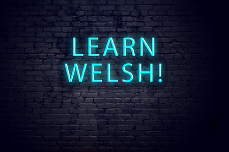 Brick wall and neon sign with inscription. Concept of learning welsh.