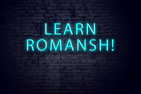 Brick wall and neon sign with inscription. Concept of learning romansh.
