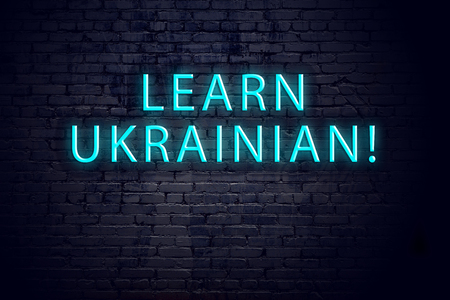 Brick wall and neon sign with inscription. Concept of learning ukrainian.