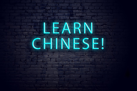 Brick wall and neon sign with inscription. Concept of learning chinese.