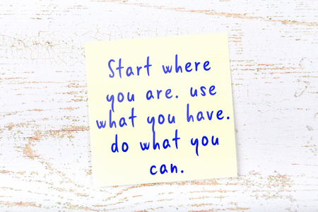 Positive inspiring quote handwritten on sticky note.