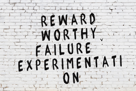 White brick wall with painted black motivational quote inscription.