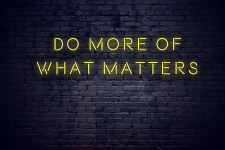 Insegna al neon con citazione motivazionale saggia positiva contro il muro di mattoni.