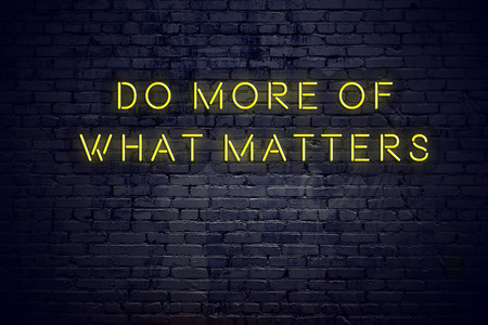 Letrero de neón con cita motivacional sabia positiva contra la pared de ladrillo.