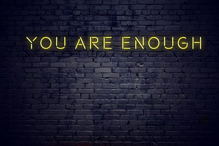Neon sign with positive wise motivational quote against brick wall . Imagens