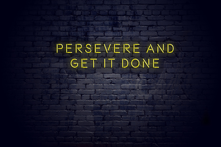 Neon sign with positive wise motivational quote against brick wall .