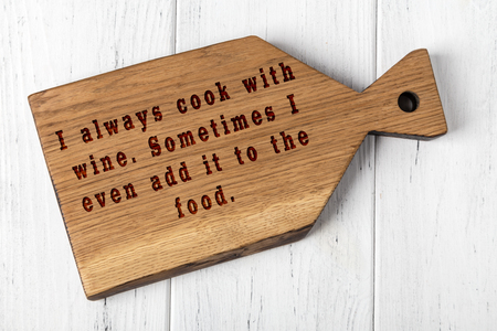 Wooden cutting board with wise inscription about food.