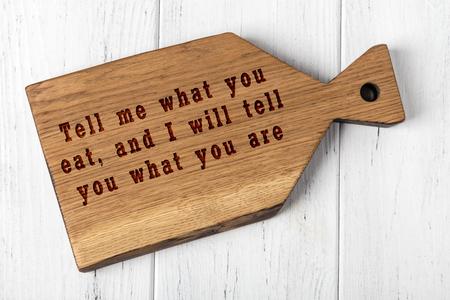 Tagliere in legno con saggia scritta sul cibo.