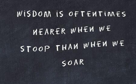 Black chalkboard with handwritten wise motivational quote . Standard-Bild
