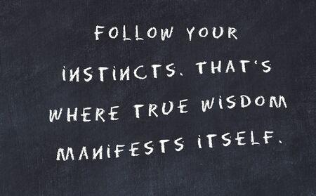 Black chalkboard with handwritten wise motivational quote . Banco de Imagens