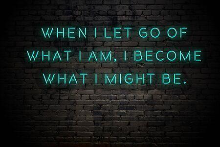 Inscripción de neón de cita motivacional sabia positiva contra la pared de ladrillo. Foto de archivo