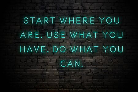 Neon inscription of positive wise motivational quote against brick wall .