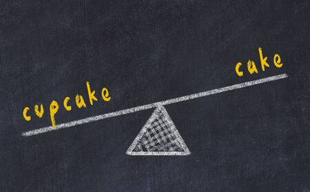 Chalk board sketch of scales. Concept of balance between cake and cupcake