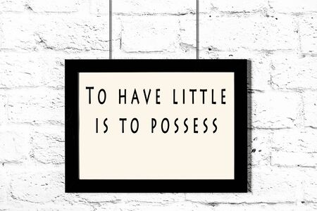 Black frame with wise quote hanging on a white brick wall. Stock Photo