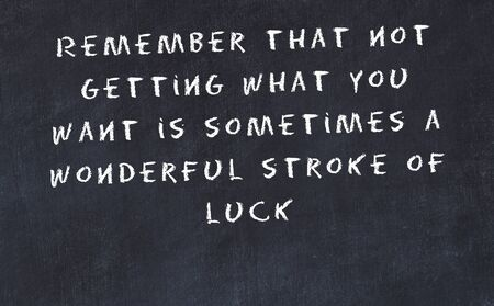 Black chalkboard with handwritten wise motivational quote . 写真素材