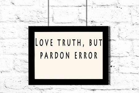 Black frame with wise quote hanging on a white brick wall. Imagens
