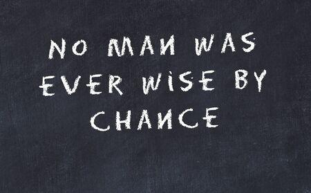 Black chalkboard with handwritten wise motivational quote .