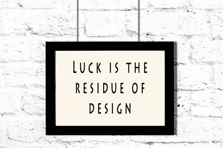 Black frame with wise quote hanging on a white brick wall. Reklamní fotografie